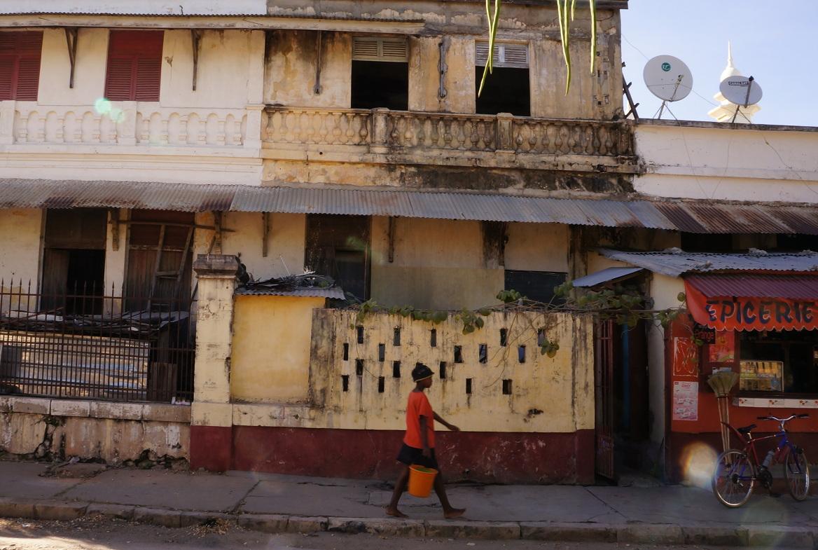 Crumbling building, girl with orange bucket