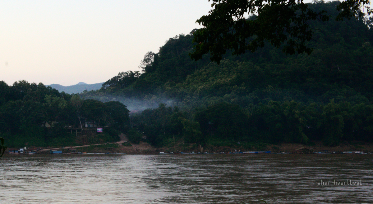 Laos: mist coming down mountain to river
