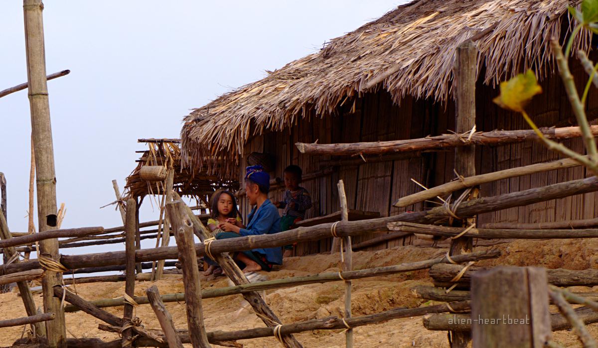 Laos-Hmong_village-sitting_in_doorway_of_hut